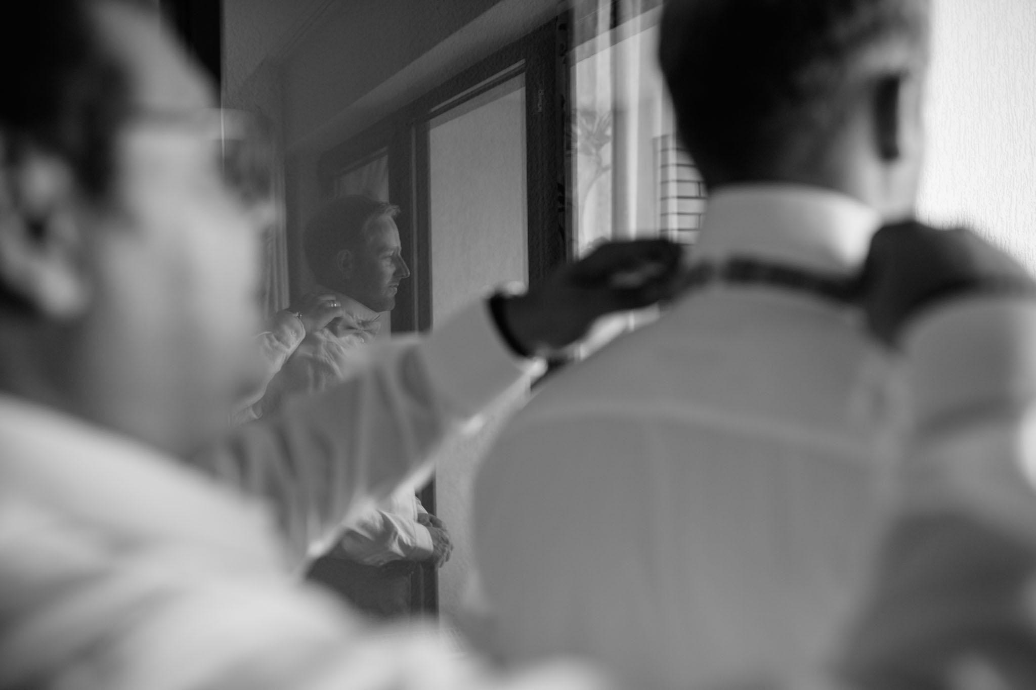 hochzeitsreportage-braeutigam-ankleiden-schwarzweiss-fliege-hotelzimmer